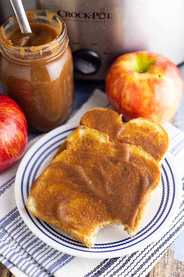 Two pieces of toast slathered in apple butter on a white and blue plate with apples, a jar or apple butter, and a stainless steel Crock Pot in the background.