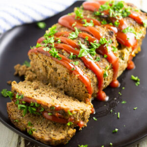 Full meatloaf on a large plate with 2 slices cut off garnished with ketchup drizzle and fresh chopped parsley.