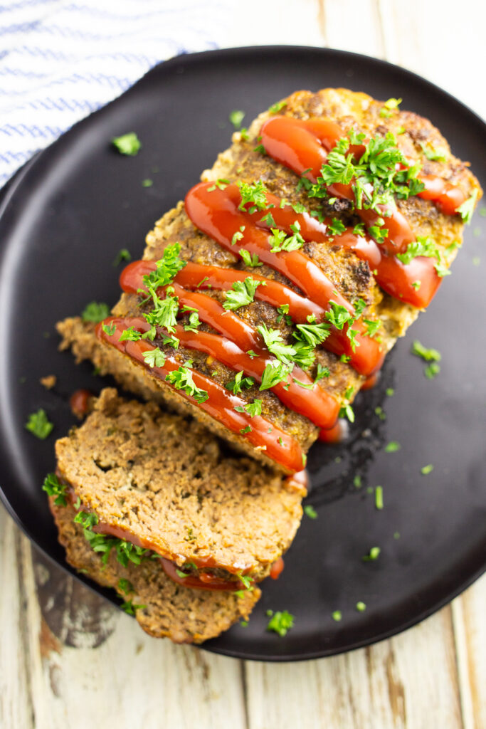 Overhead view of a full meatloaf on a large plate with 2 slices cut off garnished with ketchup drizzle and fresh chopped parsley.