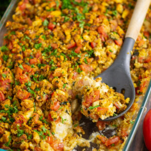 Casserole dish filled with bruschetta chicken bake with a spoonful missing and a wooden spoon in the dish.