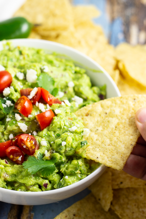 Guacamole in a bowl topped with halved cherry tomatoes, fresh cilantro, and cotija cheese with a chip dipping into and tortilla chips and a jalapeno in the background