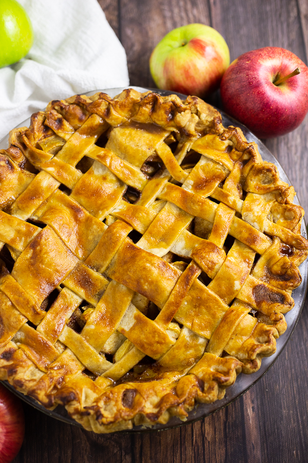 Overhead picture of a whole apple pie with a lattice crust surrounded by apples on a rustic wood background