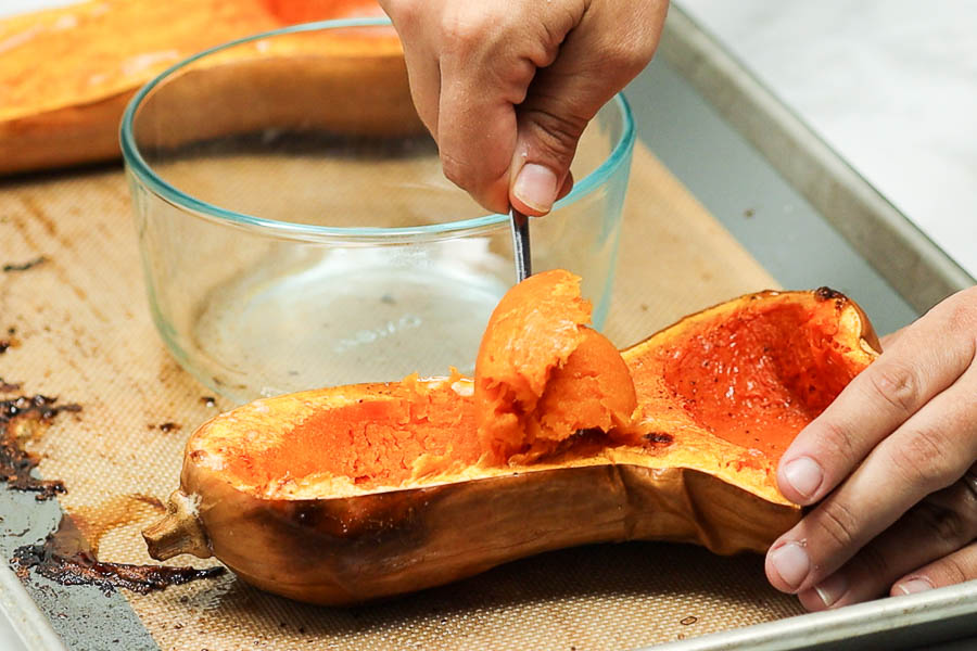 Roasted butternut squash on a baking sheet with the flesh being scooped out with a spoon into a glass bowl.
