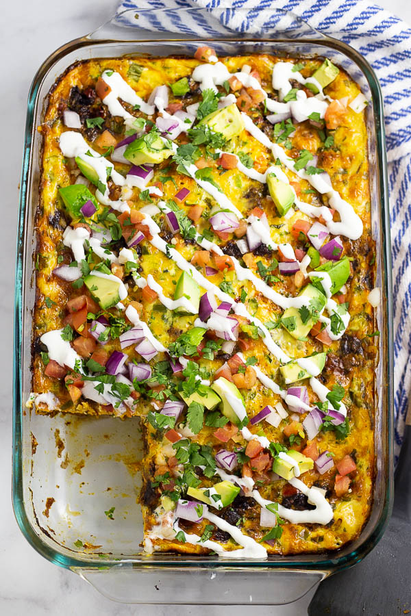 Mexican Breakfast Casserole topped with pico de gallo, red onion, avocado, and a drizzle of sour cream in a glass baking dish on a white marble background with a blue and white linen