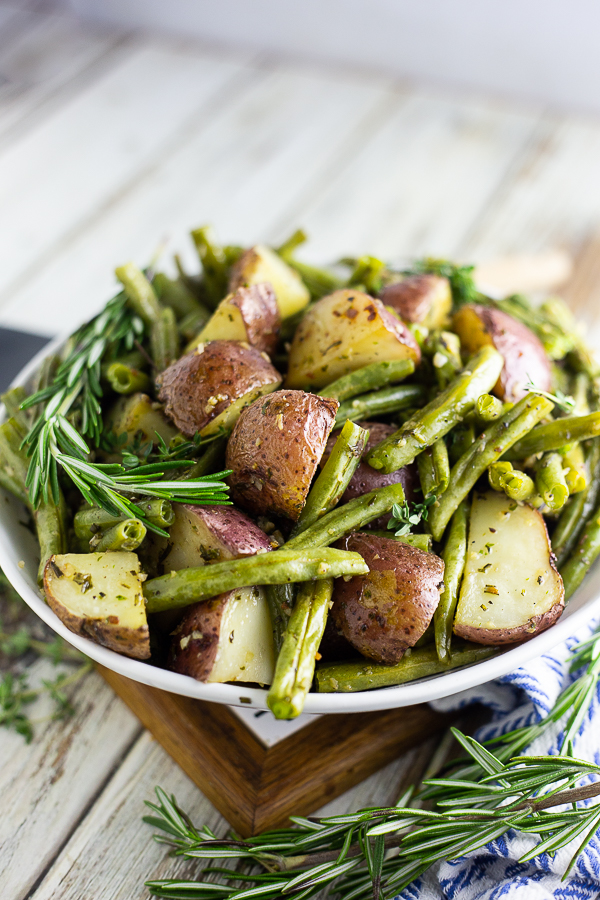 Roasted red potatoes and green beans in a white bowl with fresh rosemary sprigs on a white rustic wood background