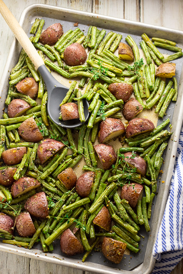 Roasted red potatoes and green beans on a large baking sheet with a gray silicone and wooden spoon on top on a white rustic wood background