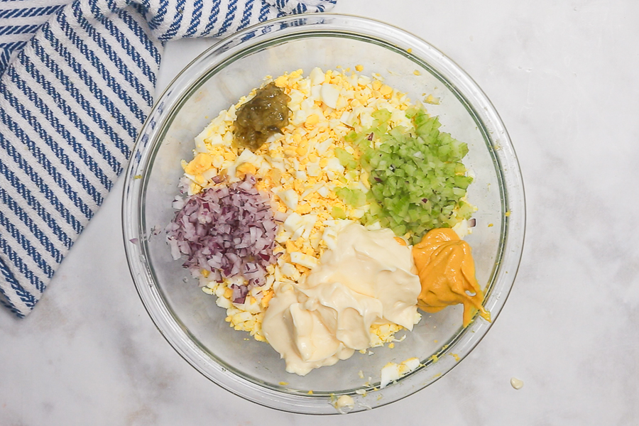 Egg salad ingredients in a glass bowl on a white marble counter