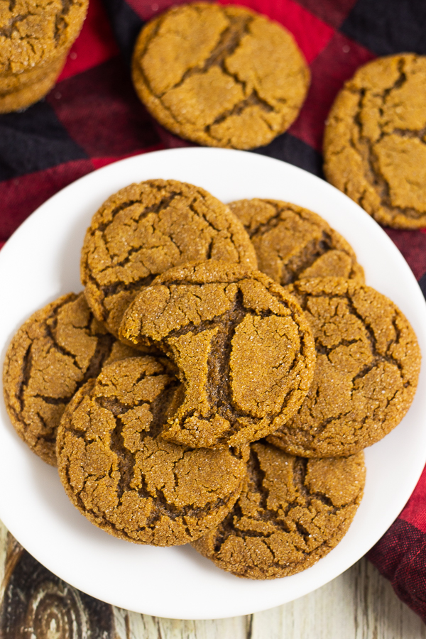 Place of gingersnaps on a red and black buffalo check linen and a white rustic wood background
