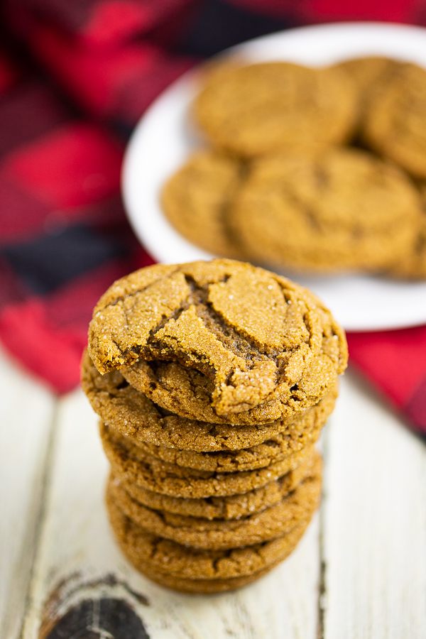 Stack of gingersnaps with a bite taken out of the top one with a plate of gingersnaps on a buffalo check linen in the background