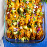 Casserole dish filled with taco stuffed shells topped with fresh avocado, red onion, and cilantro