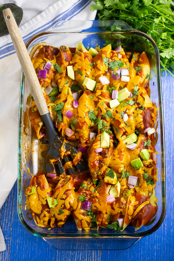 Casserole dish filled with taco stuffed shells topped with fresh avocado, red onion, and cilantro, with a wooden spoon in the middle