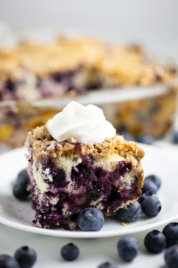Side view of blueberry buckle topped with whipped cream on a small plate with fresh blueberries with more fresh blueberries in the foreground, and the rest of the cake in the dish behind