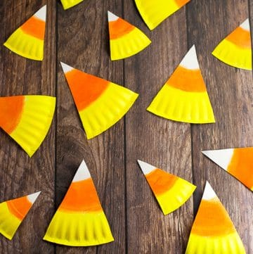 DIY Halloween Paper Plate Candy Corn Banner Tutorial - This cute and festive DIY Paper Plate Candy Corn Banner makes an adorable and cheap DIY Halloween decoration that's perfect for your home or even a Halloween party decoration.  So easy to make that even the kids could help!