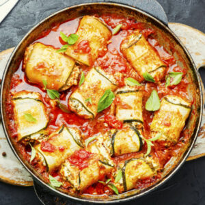 Zucchini rollatinis in a skillet with red sauce