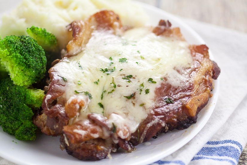 Thick cut pork chops with bacon and swiss cheese on white plate with veggies and potatoes.