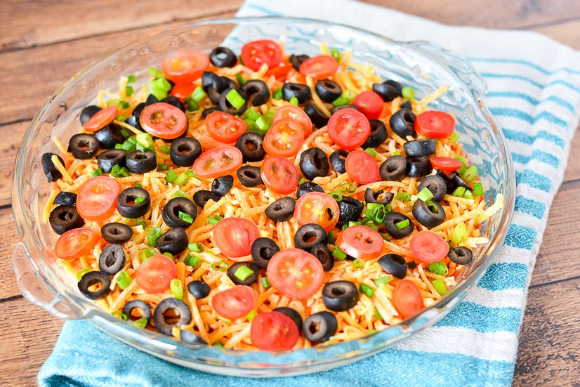 Taco Dip Recipe - Taco Dip is a super quick and easy recipe perfect for game day and parties with classic taco flavors like sour cream, beans, and salsa!  Plus, you can customize it to your own tastes!
