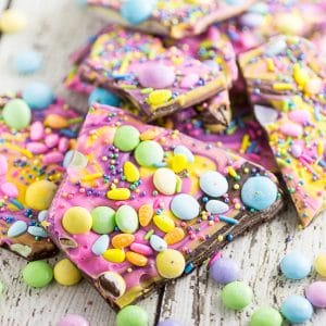 Chocolate Easter Bark is a simple, festive, spring treat featuring two kinds of chocolate swirled together and topped with M&M's, chocolate eggs, and sprinkles! The pastel colors, fun sprinkles, and candy make this a super fun and festive no bake Easter treat for kids!