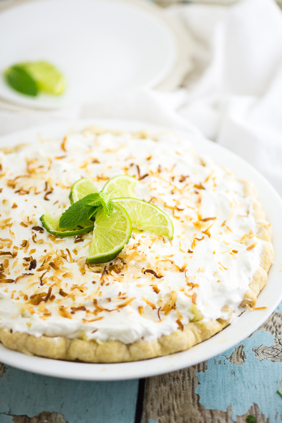 Full coconut cream pie topped with toasted coconut and lime wedges on a rustic wood background
