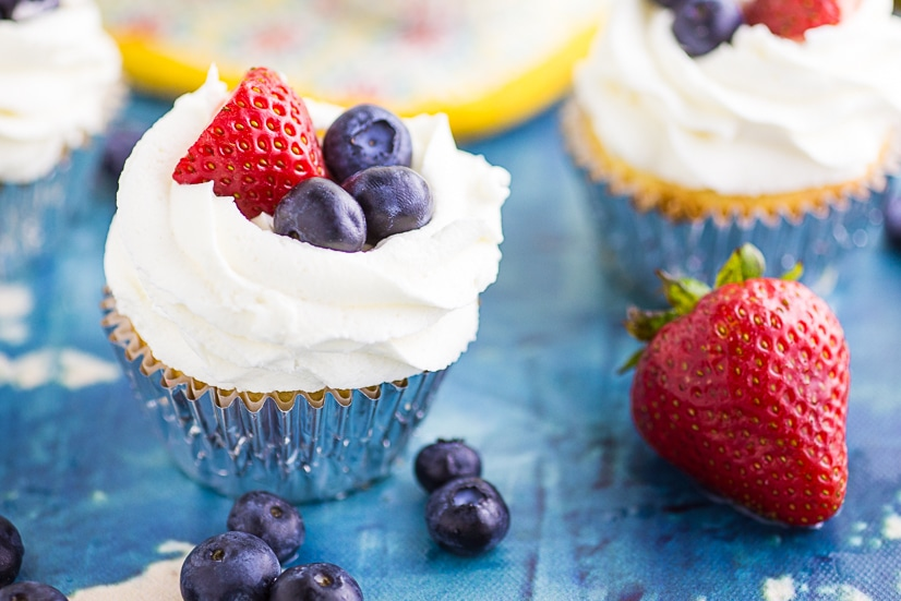 These Berries and Cream Cupcakes are made with a moist vanilla cupcake with strawberries and blueberries mixed in, filled with strawberry preserves, and topped with whipped cream cheese frosting and more fresh berries for a cupcake that is not only delicious, but perfect for summer!