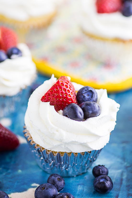Cupcake topped with strawberry and blueberries on a blue concrete background with more cupcakes in the background