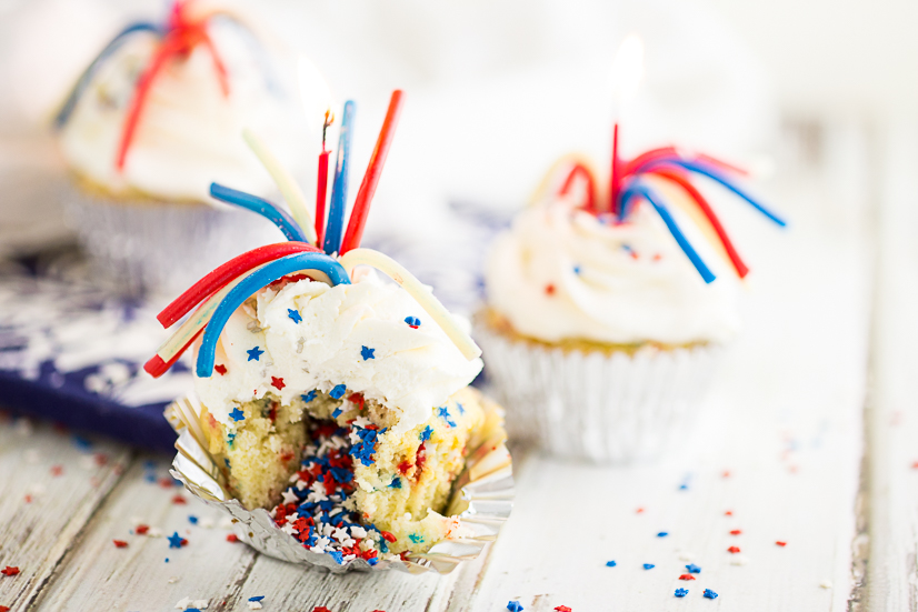 Vanilla cupcake with red, white, and blue star sprinkles, topped with a pull 'n peel twizzler and a sparkler candle on a rustic white wood background.
