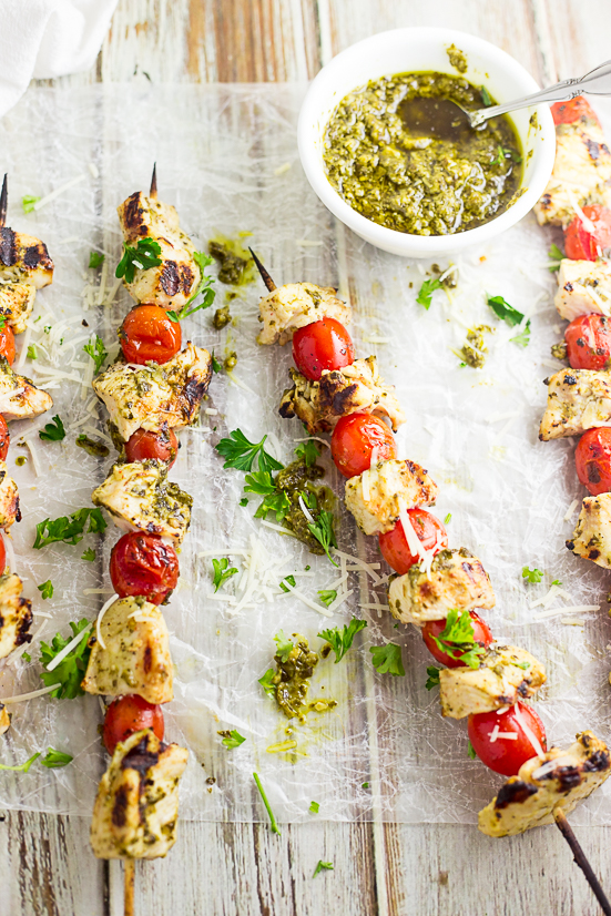 Grilled chicken and cherry tomatoes on skewers brushed with pesto sitting on wax paper with a small white bowl of pesto on a white distressed wood background