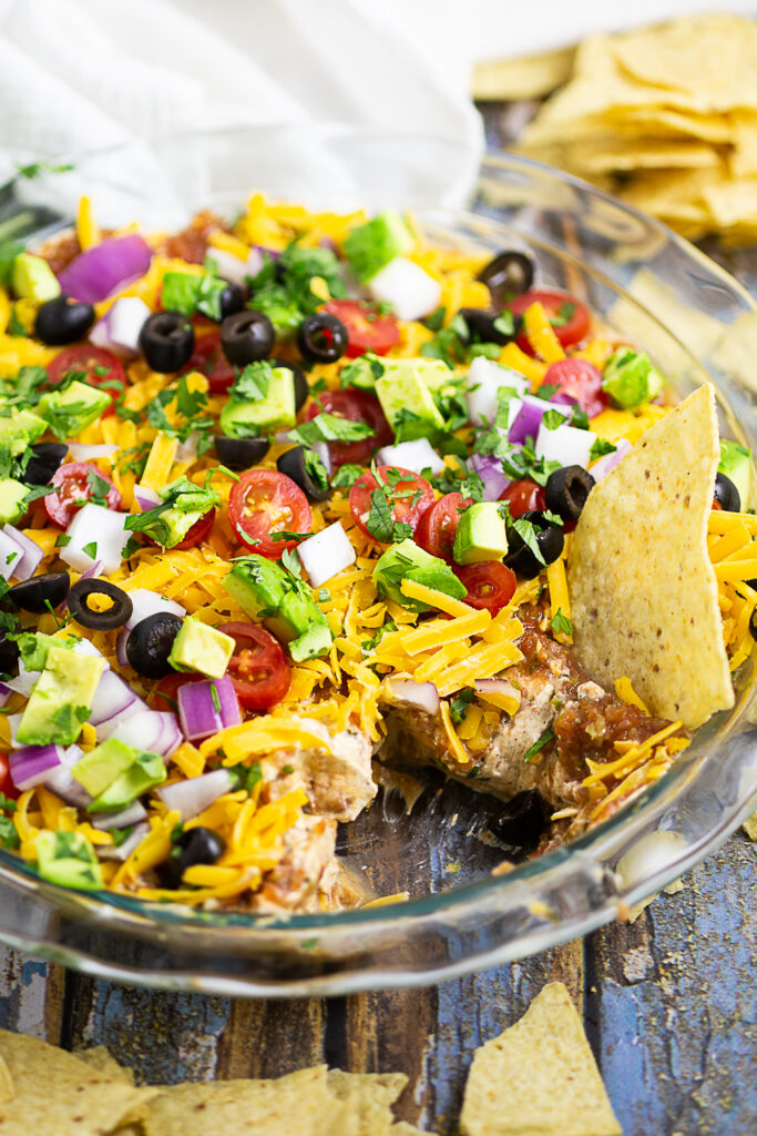 Layered taco dip in a round glass dish with a scoop missing and a chip sticking out of it. Tortilla chips and clean linen surround the dish