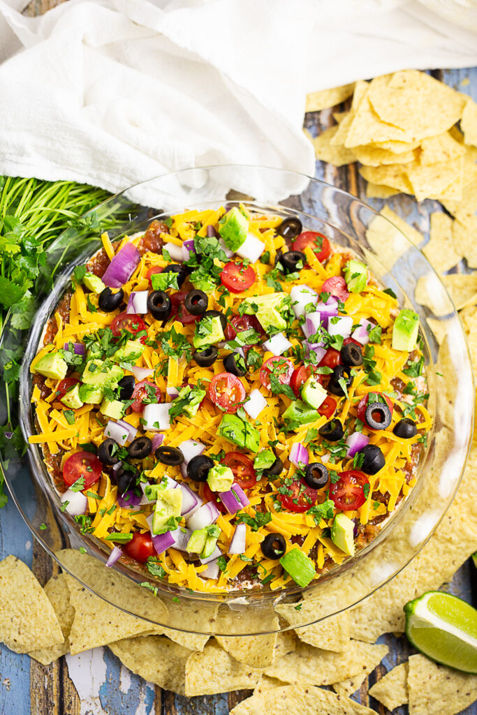 Overhead view of easy layered taco dip in a round glass dish surrounded by tortilla chips, a fresh bunch of cilantro, lime wedges and a clean linen.