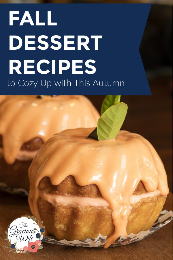 """Two mini bundt cakes stacked on each other to look like a pumpkin with orange glaze running down and a mint leaf on top. The words """"Fall Dessert Recipes to Cozy Up with This Autumn"""" are overlayed."""