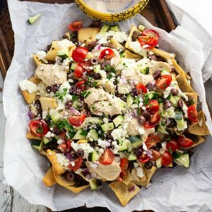 Greek Nachos on parchment paper on an old baking sheet