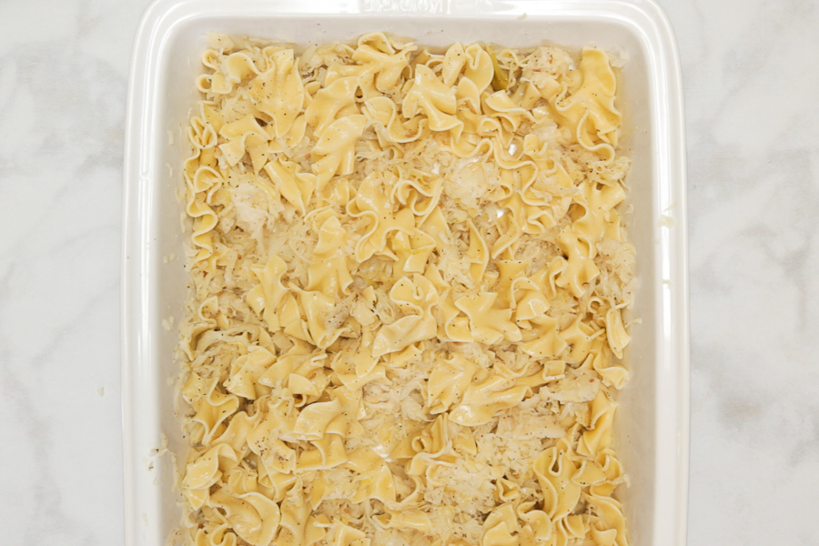 Step 1 making reuben casserole with sauerkraut and egg noodles in a ceramic casserole dish on a white marble background
