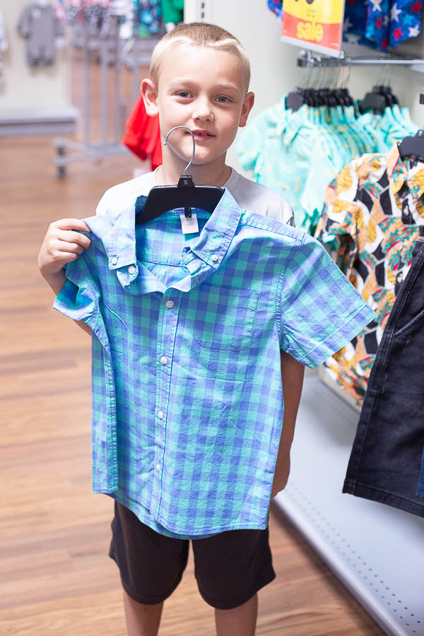 Little boy holding blue checkered collared shirt in a store.