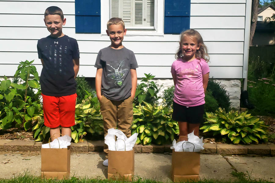 3 kids standing in front of a white house with brown bags