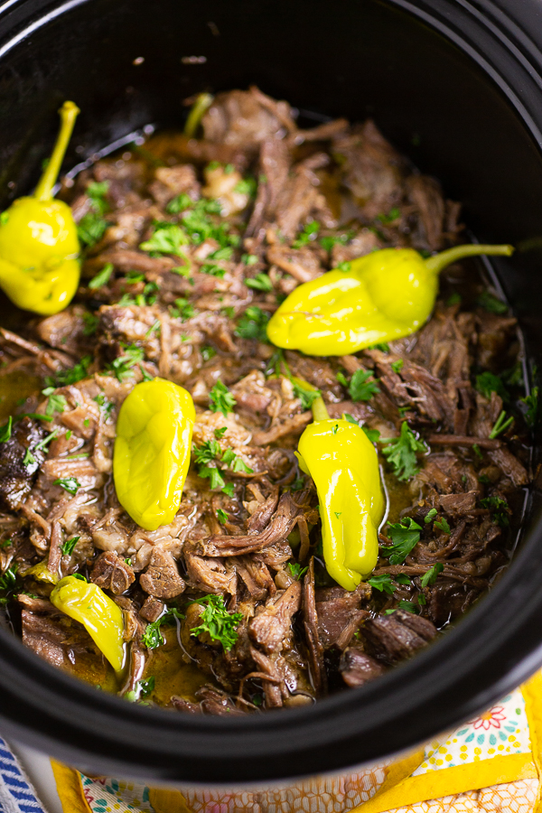 Shredded Mississippi Pot Roast with pepperoncinis and fresh parsley in a slow cooker crock