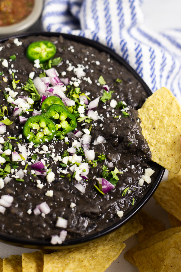 Refried black beans topped with cotija cheese, jalapenos, and red onion in a black matte bowl with a chip dipping in