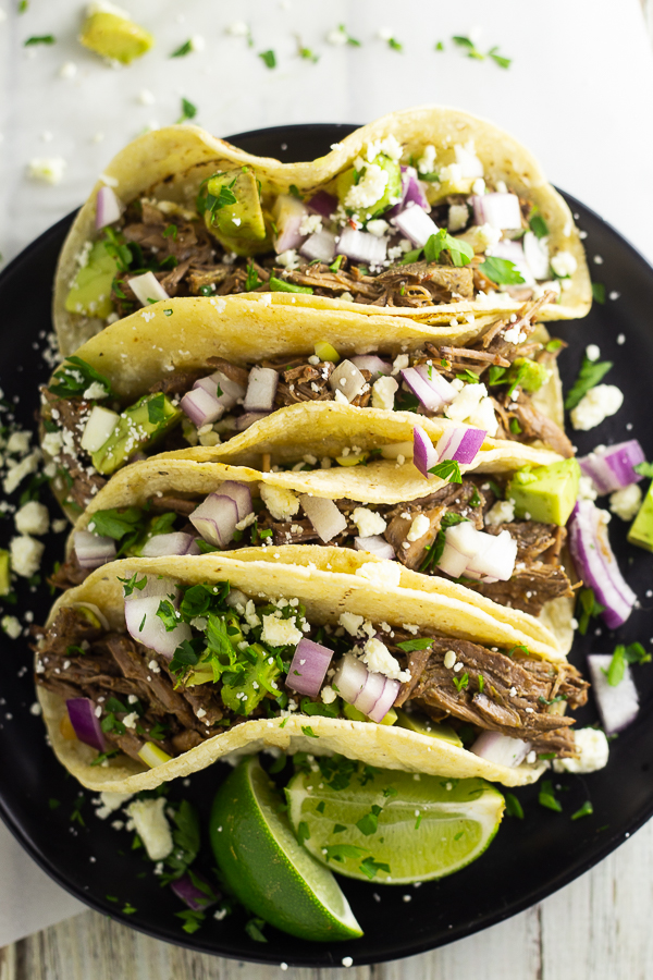 4 street tacos on a black plate stuffed with Chipotle barbacoa, cilantro, redo onion, and queso fresco.