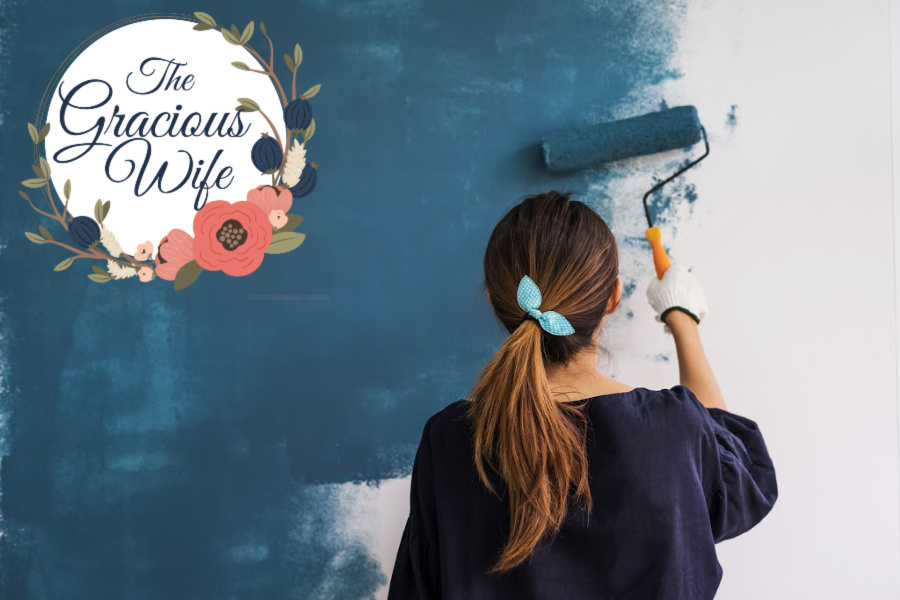 Girl with ponytail painting a wall with a paint roller