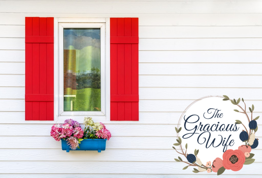 White house with red window shutters, and a bright window basket with flowers