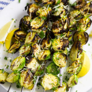Grilled brussels sprouts on skewers on a plate with lemon wedges topped with grated Parmesan
