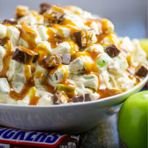 Snickers Caramel Apple Salad drizzled with caramel sauce in a large bowl next to a wrapped Snickers bar and Granny Smith Apple on a rustic wood backdrop