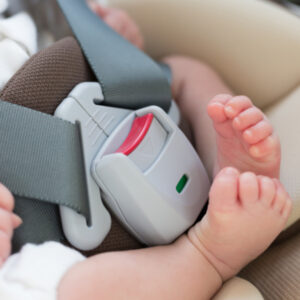 Baby feet next to a car seat buckle