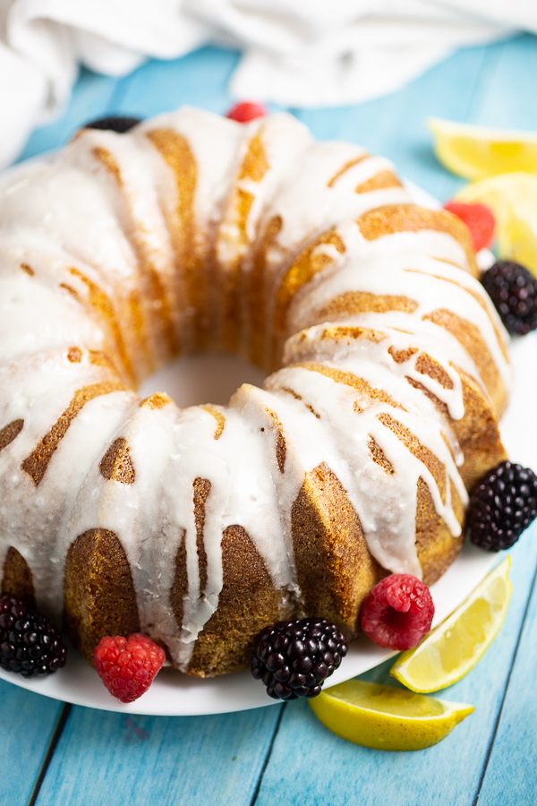 Lemon buttermilk pound cake with lemon glaze on a large plate surrounded by fresh blackberries and raspberries and lemon wedges