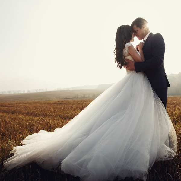 Man and woman couple embracing outdoors wearing a wedding dress and a suit