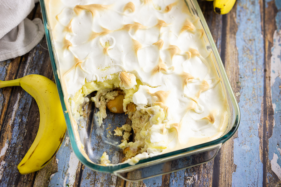 Overhead picture of southern banana pudding topped with meringue next to a banana on a rustic wood background