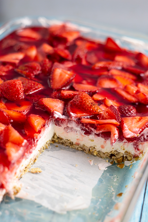 Strawberry pretzel salad in a glass casserole dish with several pieces cut out so you can see the crust, cream cheese, and strawberry layers.