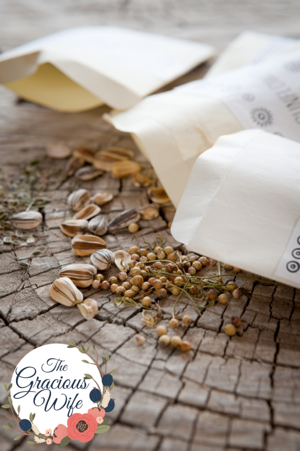 Brown packets of seeds laying out on rustic wood