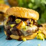 Bourbon teriyaki Hawaiian burger with teriyaki sauce running down on a sesame seed bun a pineapple in the background