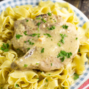 Two Crock Pot Ranch Pork chops garnished with fresh parsley on a bed of buttery egg noodles in front of a slow cooker.