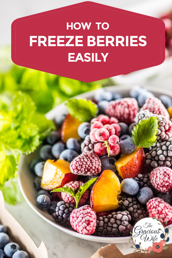 """Frozen berries in a bowl with mint leave behind it and the words """"how to freeze berries easily"""" at the top"""