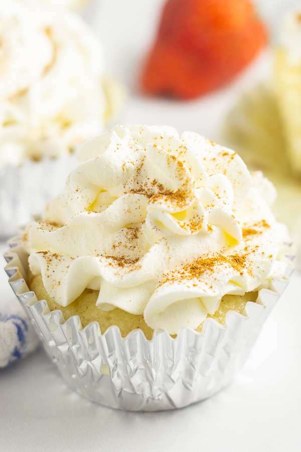 Close up of a cupcake in a foil wrapper topped with whipped mascarpone frosting and a sprinkle of cinnamon